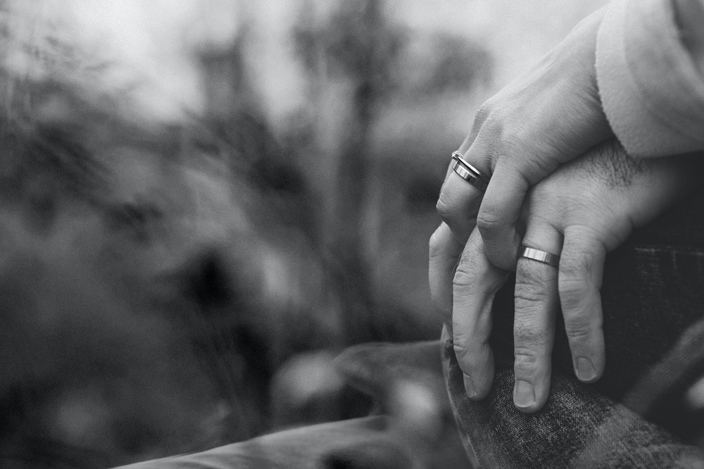 Predatory marriage: black and white image of two hands wearing weddings rings.